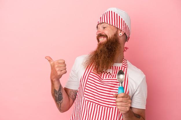 Jeune homme de race blanche au gingembre avec une longue barbe tenant une boule isolée sur des points de fond rose avec le pouce loin, riant et insouciant.