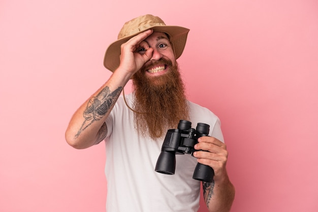 Jeune homme de race blanche au gingembre avec une longue barbe tenant des jumelles isolées sur fond rose excité en gardant le geste ok sur les yeux.