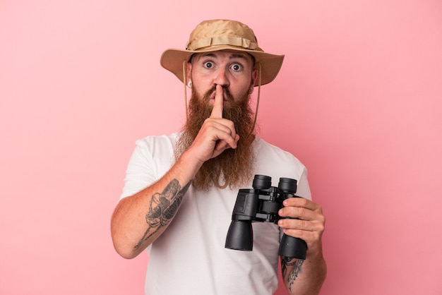 Jeune homme de race blanche au gingembre avec une longue barbe tenant des jumelles isolées sur fond rose gardant un secret ou demandant le silence.
