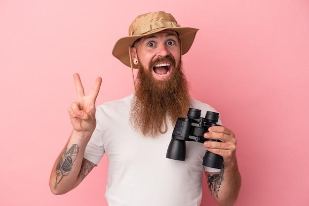Jeune homme de race blanche au gingembre avec une longue barbe tenant des jumelles isolées sur fond rose joyeux et insouciant montrant un symbole de paix avec les doigts.