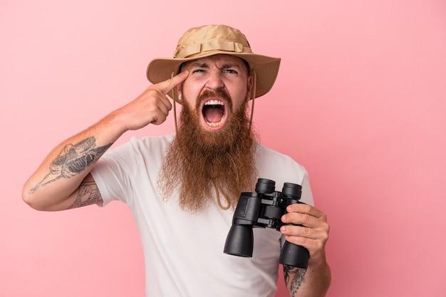 Jeune homme de race blanche au gingembre avec une longue barbe tenant des jumelles isolées sur fond rose montrant un geste de déception avec l'index.