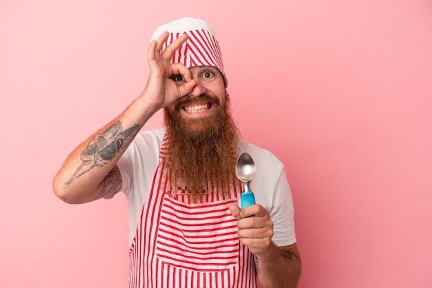 Jeune homme de race blanche au gingembre avec une longue barbe tenant un scoop isolé sur fond rose excité en gardant le geste ok sur les yeux.