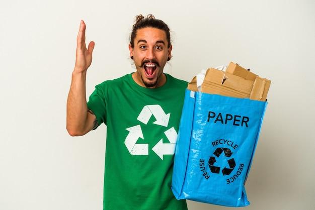 Jeune homme de race blanche aux cheveux longs en carton de recyclage isolé sur fond blanc recevant une agréable surprise, excité et levant les mains.