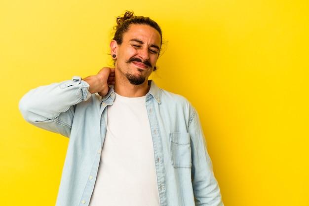 Jeune homme de race blanche aux cheveux longs isolé sur fond jaune ayant une douleur au cou due au stress, en le massant et en le touchant avec la main.