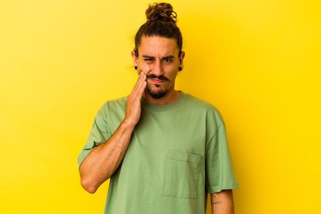 Jeune homme de race blanche aux cheveux longs isolé sur fond jaune ayant une forte douleur dentaire, une douleur molaire.