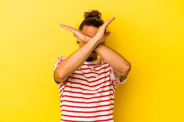 Jeune homme de race blanche aux cheveux longs isolé sur fond jaune en gardant les deux bras croisés, concept de déni.