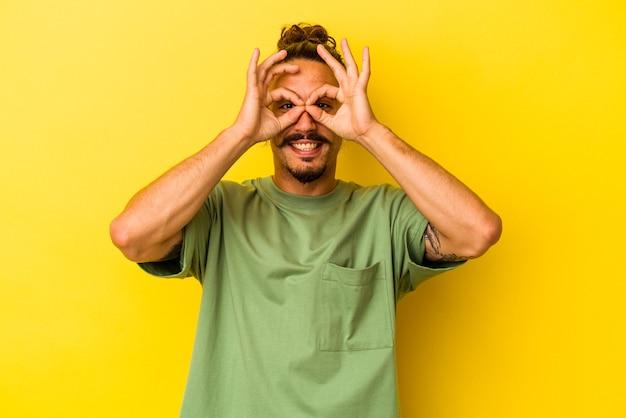 Jeune homme de race blanche aux cheveux longs isolé sur fond jaune montrant un signe d'accord sur les yeux