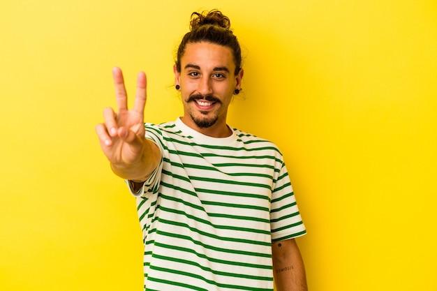 Jeune homme de race blanche aux cheveux longs isolé sur fond jaune montrant le signe de la victoire et souriant largement.