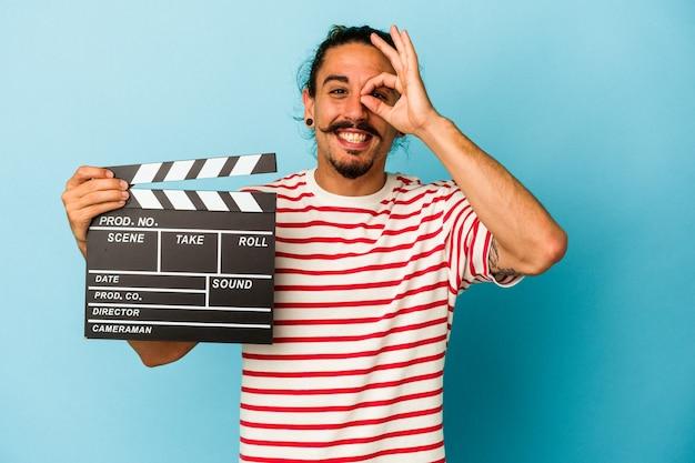 Jeune homme de race blanche aux cheveux longs tenant un clap isolé sur fond bleu excité en gardant le geste ok sur les yeux.