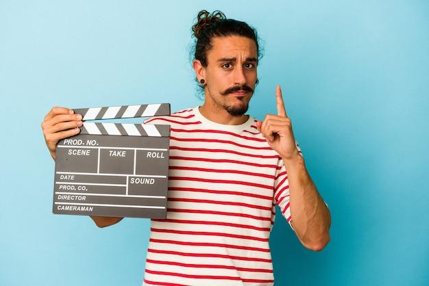 Jeune homme de race blanche aux cheveux longs tenant un clap isolé sur fond bleu montrant le numéro un avec le doigt.