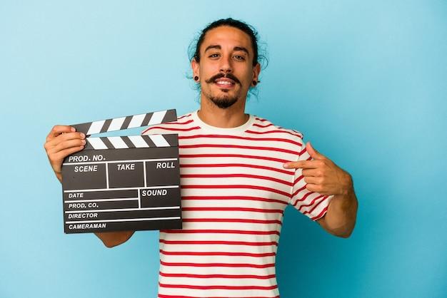 Jeune homme de race blanche aux cheveux longs tenant un clap isolé sur fond bleu personne pointant à la main vers un espace de copie de chemise, fier et confiant