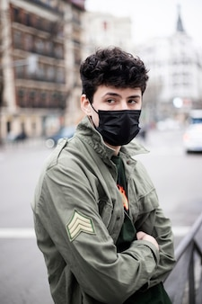 Jeune homme de race blanche aux cheveux noirs avec les bras croisés et un masque de protection contre l'infection à covid dans la rue