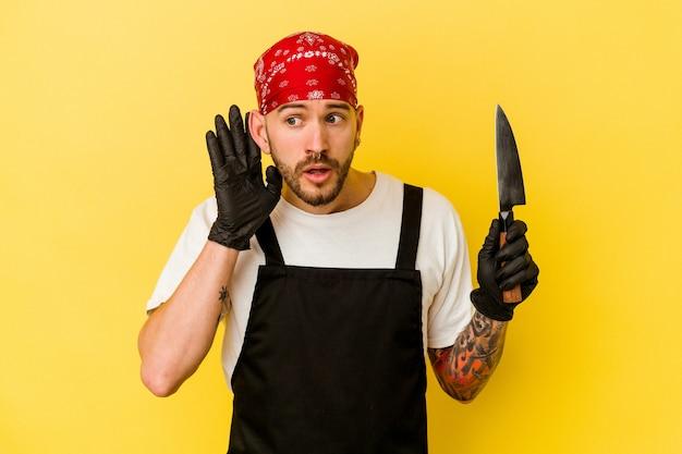 Jeune homme de race blanche batcher tatoué tenant un couteau isolé sur fond jaune en essayant d'écouter un commérage.