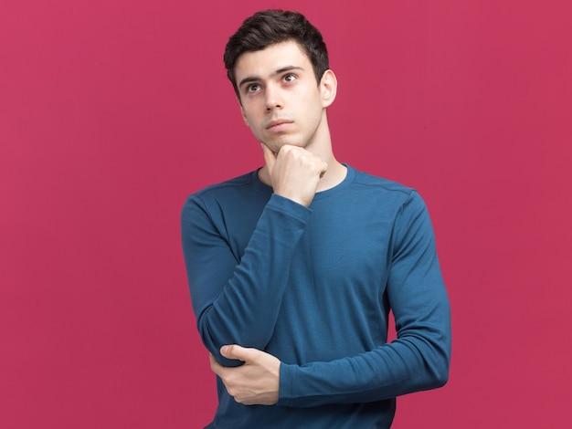 Un jeune homme de race blanche brune réfléchie met la main sur le menton en regardant le côté isolé sur un mur rose avec un espace de copie