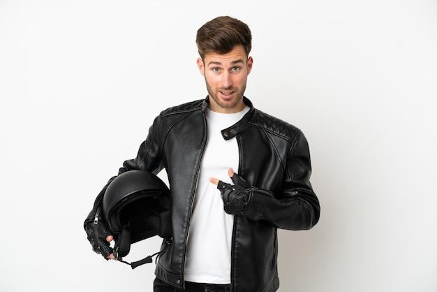 Jeune homme de race blanche avec un casque de moto isolé sur fond blanc avec une expression faciale surprise