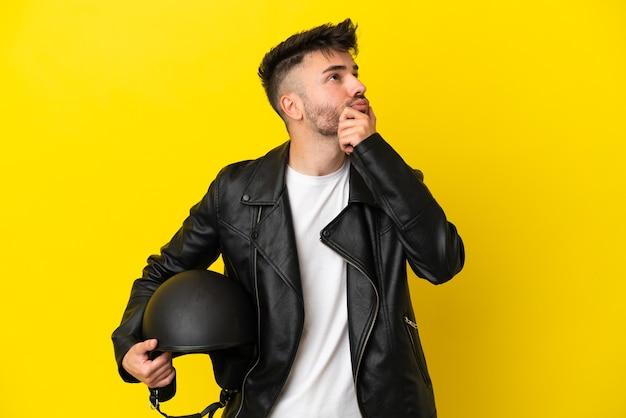 Jeune homme de race blanche avec un casque de moto isolé sur fond jaune ayant des doutes