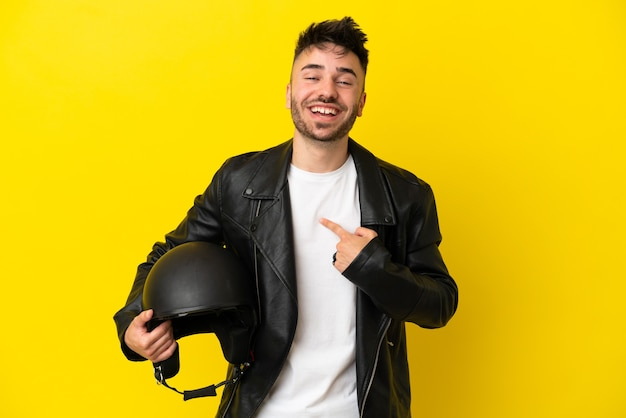 Jeune homme de race blanche avec un casque de moto isolé sur fond jaune avec une expression faciale surprise