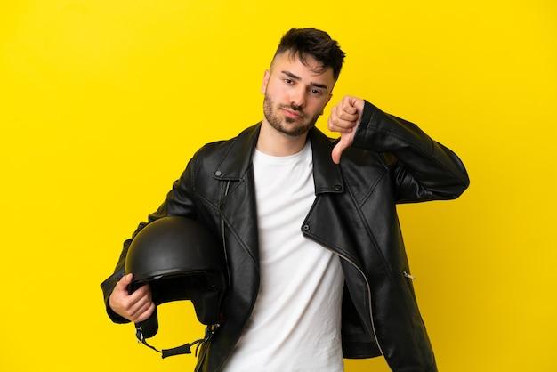 Jeune homme de race blanche avec un casque de moto isolé sur fond jaune montrant le pouce vers le bas avec une expression négative