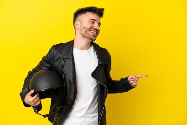 Jeune homme de race blanche avec un casque de moto isolé sur fond jaune, pointant le doigt sur le côté et présentant un produit