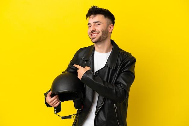 Jeune homme de race blanche avec un casque de moto isolé sur fond jaune pointant vers l'arrière