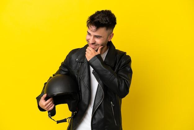 Jeune homme de race blanche avec un casque de moto isolé sur fond jaune regardant sur le côté et souriant