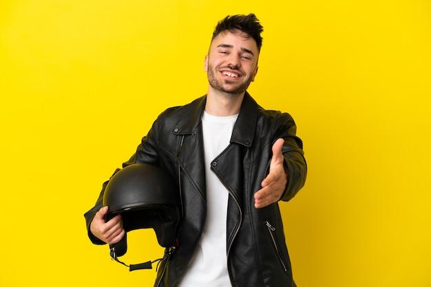 Jeune homme de race blanche avec un casque de moto isolé sur fond jaune se serrant la main pour conclure une bonne affaire