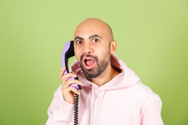 Jeune homme de race blanche chauve en sweat à capuche rose isolé, maintenez le téléphone fixe avec heureux visage étonné excité