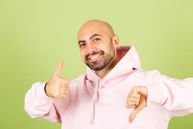 Jeune homme de race blanche chauve en sweat à capuche rose isolé, positif un pouce vers le haut un vers le bas