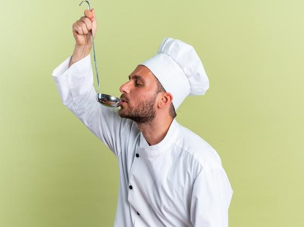Jeune homme de race blanche concentré cuisinier en uniforme de chef et casquette debout en vue de profil buvant à la louche