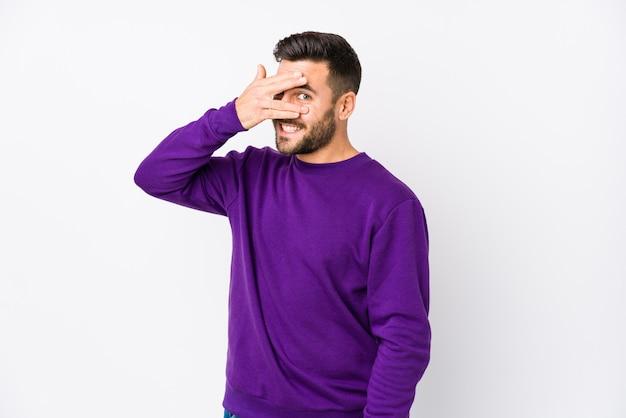Jeune homme de race blanche contre un mur blanc isolé cligner des yeux à travers les doigts, embarrassé couvrant le visage.