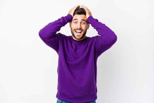 Jeune homme de race blanche contre un mur blanc rit joyeusement en gardant les mains sur la tête