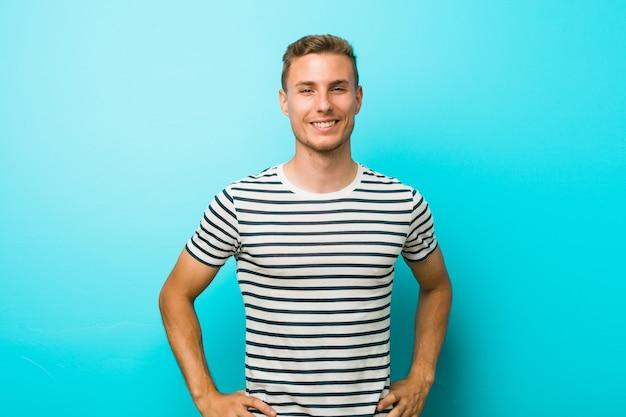 Jeune homme de race blanche contre un mur bleu confiant en gardant les mains sur les hanches.