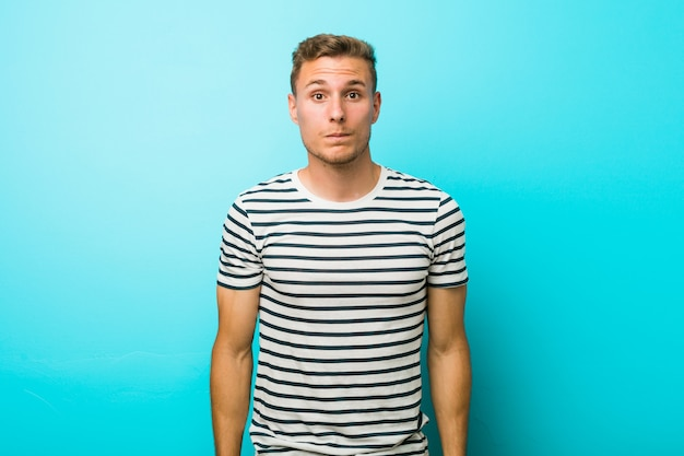 Jeune homme de race blanche contre un mur bleu hausse les épaules et les yeux ouverts confus.