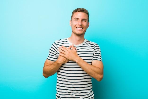 Jeune homme de race blanche contre un mur bleu en riant en gardant les mains sur le coeur, concept de bonheur.