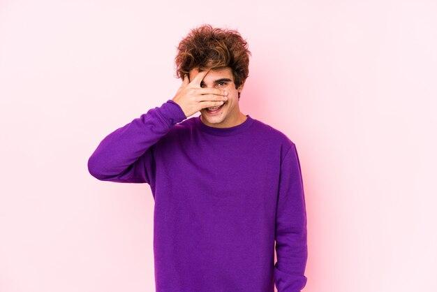 Jeune homme de race blanche contre un mur rose isolé cligner des yeux à la caméra à travers les doigts, embarrassé couvrant le visage.