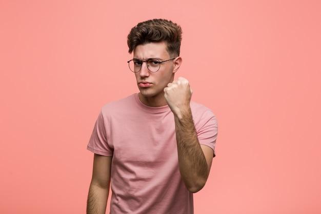 Jeune homme de race blanche cool montrant le poing à la caméra, expression faciale agressive
