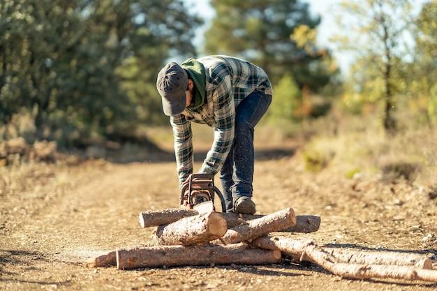 Jeune homme de race blanche coupant un tronc d'arbre avec une tronçonneuse