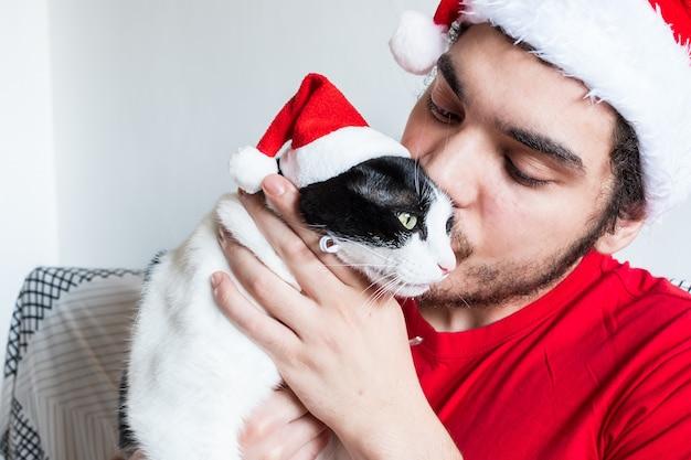 Jeune homme de race blanche dans un chapeau de père noël s'embrasser avec son chat noir et blanc