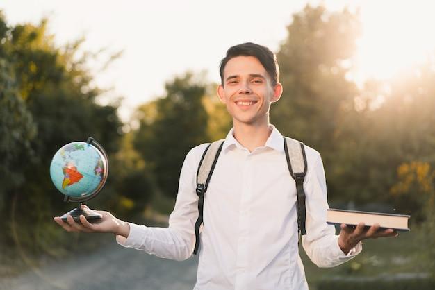Un jeune homme de race blanche dans une chemise classique blanche avec un sac à dos gris sur le dos tient un globe et un livre bleu dans différentes mains sur la nature et la lumière du soleil. concept d'éducation