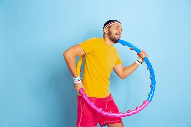 Jeune homme de race blanche dans des vêtements lumineux formation sur l'espace bleu concept de sport, émotions humaines, expression faciale, mode de vie sain, jeunesse, ventes