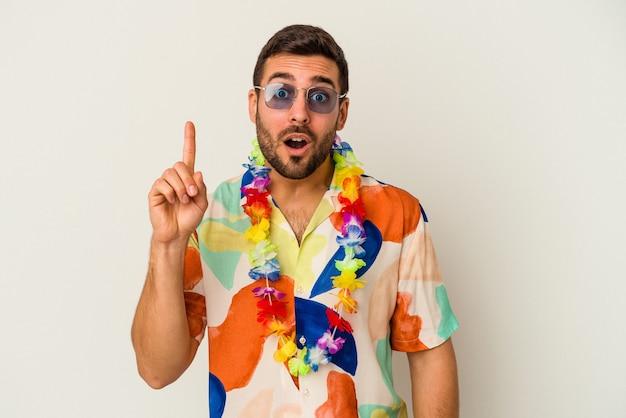Jeune homme de race blanche dansant sur une fête hawaïenne isolée sur fond blanc ayant une bonne idée, concept de créativité.