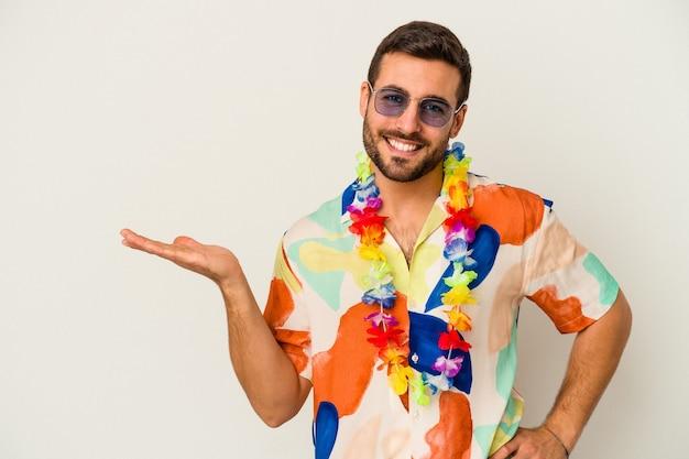 Jeune homme de race blanche dansant sur une fête hawaïenne isolée sur un mur blanc montrant un espace de copie sur une paume et tenant une autre main sur la taille