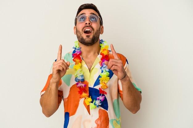 Jeune homme de race blanche dansant sur une fête hawaïenne isolée sur un mur blanc pointant vers le haut avec la bouche ouverte