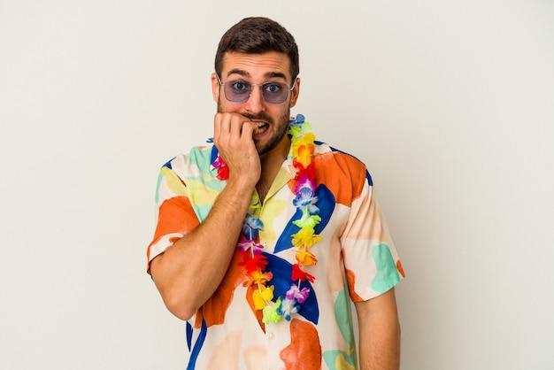 Jeune homme de race blanche dansant sur une fête hawaïenne isolée sur un mur blanc se mordant les ongles, nerveux et très anxieux