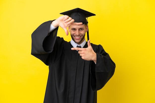 Jeune homme de race blanche diplômé universitaire isolé sur fond jaune se concentrant sur le visage. symbole d'encadrement