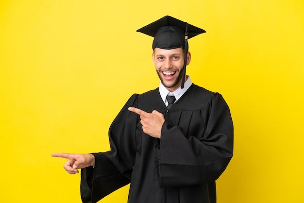 Jeune homme de race blanche diplômé universitaire isolé sur fond jaune surpris et pointant du côté