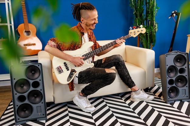 Jeune homme de race blanche avec des dreadlocks jouant de la guitare électrique dans sa chambre
