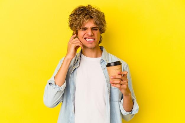Jeune homme de race blanche avec du maquillage tenant un café à emporter isolé sur fond jaune couvrant les oreilles avec les mains.