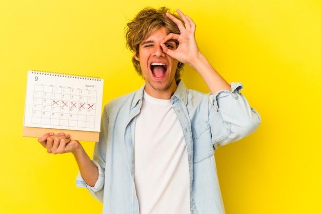 Jeune homme de race blanche avec du maquillage tenant un calendrier isolé sur fond jaune excité en gardant le geste ok sur les yeux.