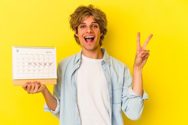 Jeune homme de race blanche avec du maquillage tenant un calendrier isolé sur fond jaune joyeux et insouciant montrant un symbole de paix avec les doigts.